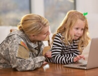 photo military parent and child using laptop at home