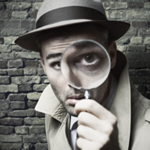 photo: PI man with magnifying glass to eye