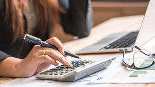 photo of woman using calculator