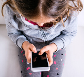 photo of young girl texting on smartphone