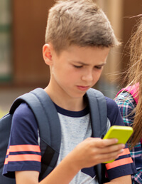 young school boy with cell phone