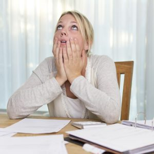 photo: woman looking up with divorce papers scattered on the table